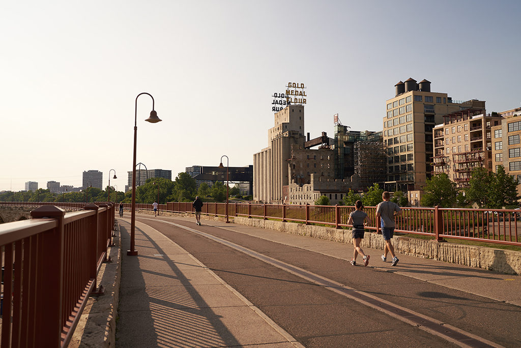 Couple running on stone arch bridge in minneapolis